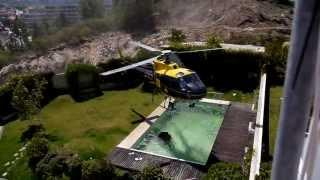 Helicopter pilot taking water from swimming pool