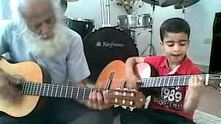 6 years old boy playing guitar